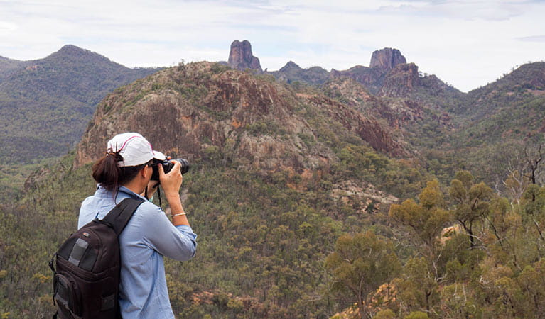 A bushwalker photographs the Warrumbungle Range from the top of Fans Horizon walking track. Photo: Leah Pippos/OEH.
