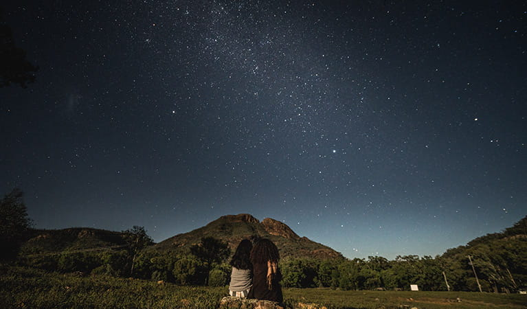 Two women sit side-by-side, stargazing in Warrumbungle National Park. Photo: Robert Mulally/OEH