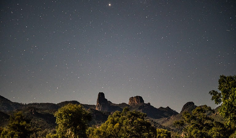 A starry night view across the Grand High Tops rock formation in Warrumbungle National Park. Photo: Robert Mulally/OEH