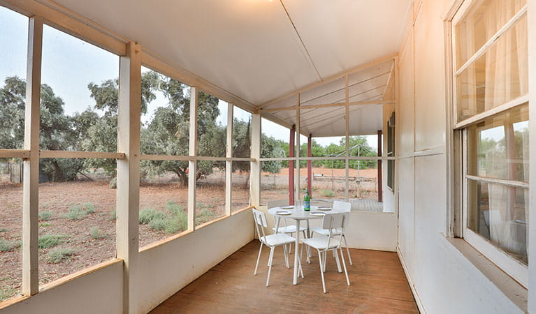 Enclosed verandah with table and chairs at Willandra Cottage, Willandra National Park. Photo: Vision House Photography/DPIE