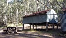 View of Sheepskin Hut and picnic table set in Wollemi bushland. Photo: Shayne Forty/OEH