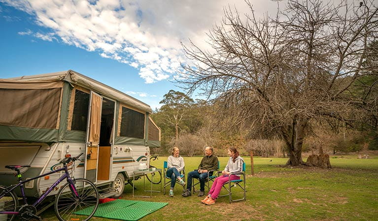 Family having breakfast around their caravan at Wombeyan Caves campground. Photo: OEH/John Spencer
