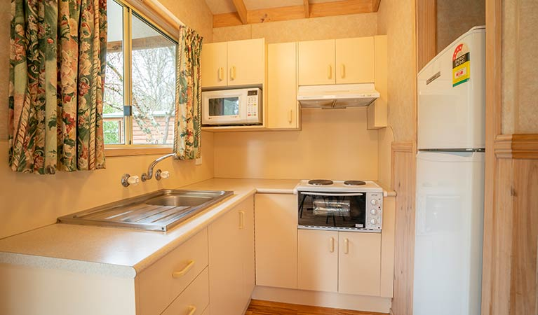 Kitchen with fridge, microwave, stove-top oven and sink in one of the Wombeyan Caves cabins. Photo: OEH/John Spencer