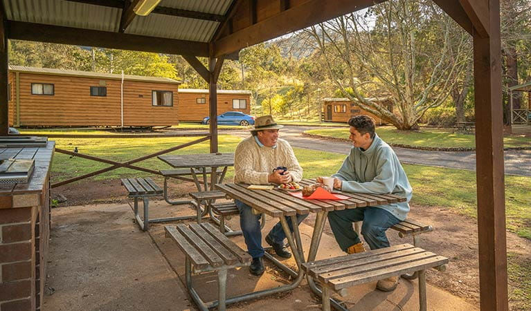 Barbecue and picnic tables under shelter at Wombeyan Caves cabins. Photo: OEH/John Spencer