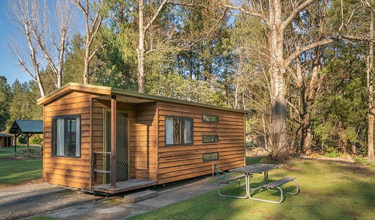 One of the smaller, standard cabins with a picnic table out the front. Photo: OEH/John Spencer