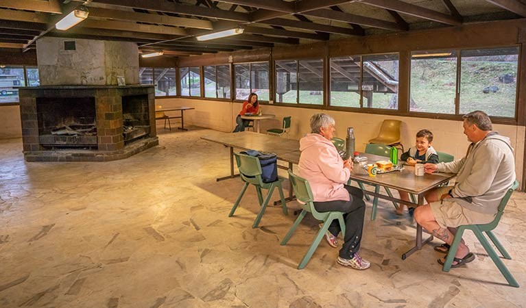 Family eating lunch in the dining hall with fireplace in background. Photo: OEH/John Spencer