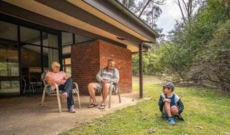 Family sitting outside Wombeyan Caves dormitories. Photo: OEH/John Spencer