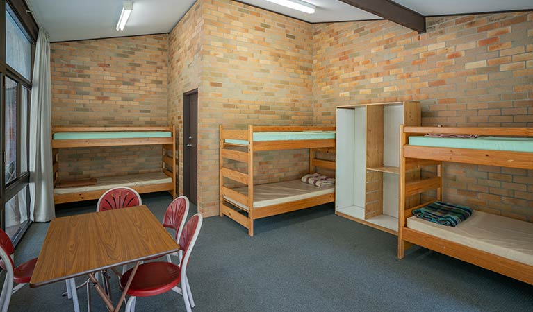 Three bunks beds and a communal table in one of the rooms in Wombeyan Caves dormitories. Photo: OEH/John Spencer