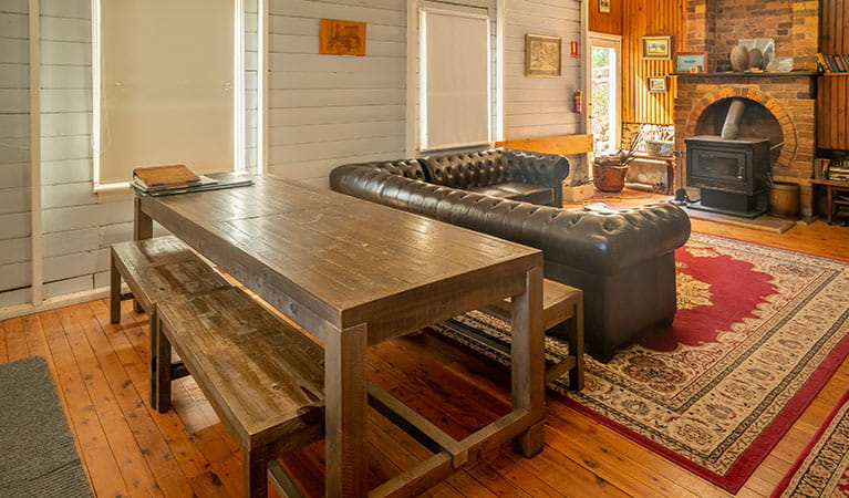 A long wooden dining table, sofa and wood heater at Post Office Lodge in Yerranderie Regional Park. Photo: John Spencer/OEH