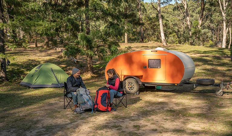 A couple preparing for a hike in front of their mini camper trailer at Private Town campground, Yerranderie Regional Park. Photo: John Spencer/OEH