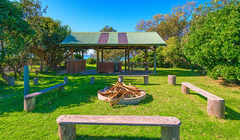 An area with benches and a firepit, perfect for groups at Illaroo group camping area in Yuraygir National Park. Photo: Jessica Robertson © DPIE
