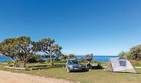 A tent pitched next to a car with the beach in the background at Red Cliff campground in Yuraygir National Park. Photo: Robert Cleary/DPIE