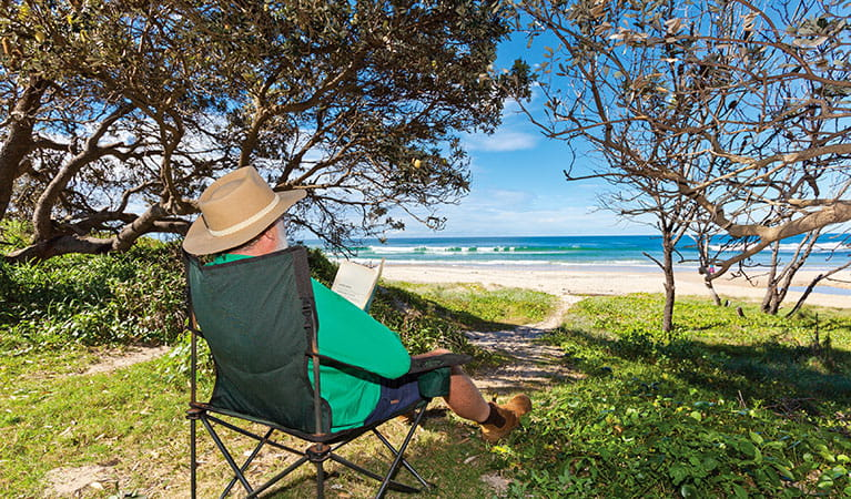 A man reads a book in the shade with a view of the beach in Red Cliff campground, Yuraygir National Park. Photo: Robert Cleary/DPIE