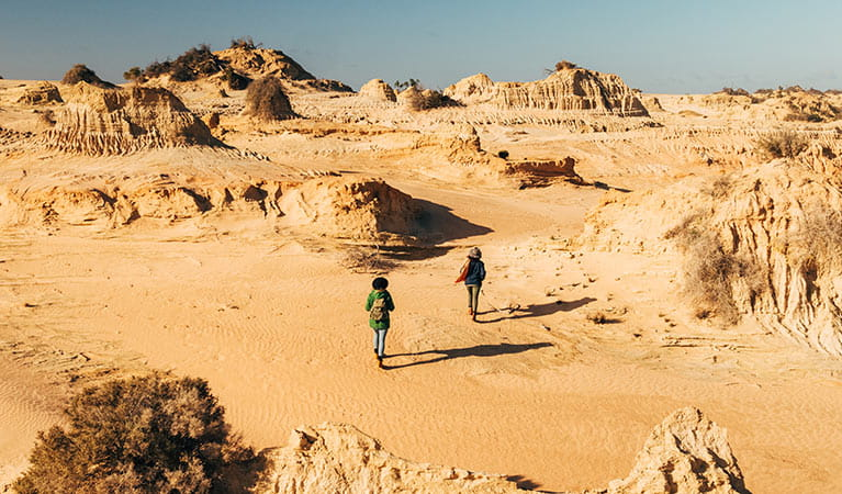 Two women walking at Walls of China in Mungo National Park. Photo: Melissa Findley © DPIE
