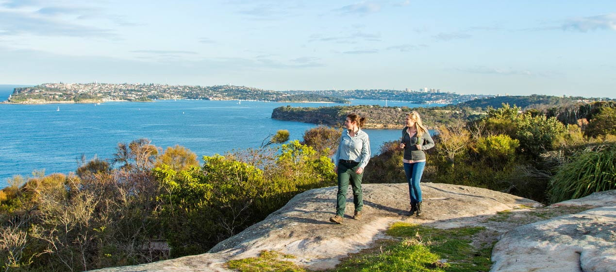 Two women walk along Manly Scenic Walk, near Dobroyd Head, Sydney Harbour National Park. Photo: Simone Cottrell © DPIE