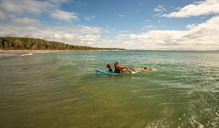 A father and young son swim on a paddle board in Bundjalung National Park. Photo: John Spencer/OEH