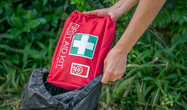 Person pulling a first aid kit out of a backpack. Photo: John Spencer/DPIE