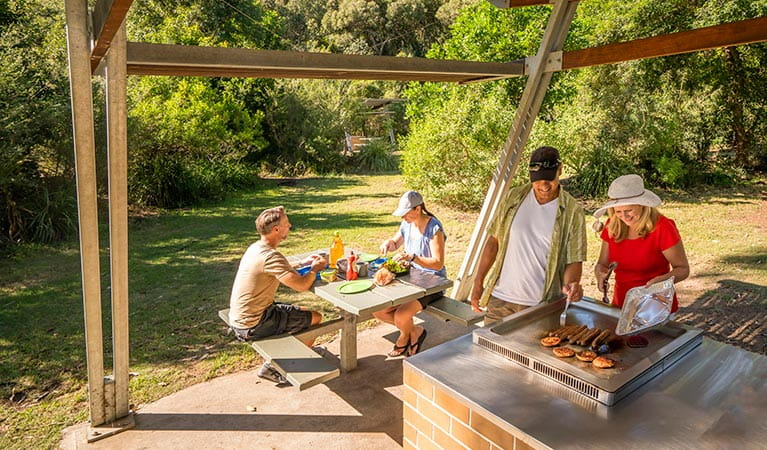 Campers cooking sausages on an NPWS-installed electric barbecue at Putty Beach campground. Photo: John Spencer/DPIE