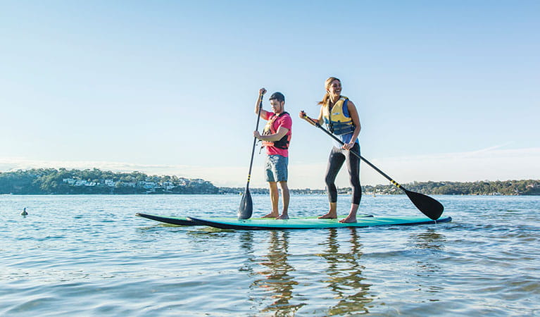 2 people stand up paddle boarding Bonnie Vale Royal National Park. Simone Cottrell/DPIE