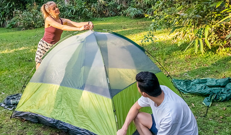 2 campers setting up a tent on the grass. Photo: John Spencer/DPIE