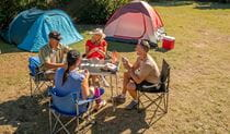 A group of friends playing cards next to their tents. Photo: John Spencer/DPIE
