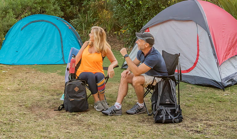 2 campers sitting with their backpacks with their tents set up in the background. Photo: John Spencer/DPIE