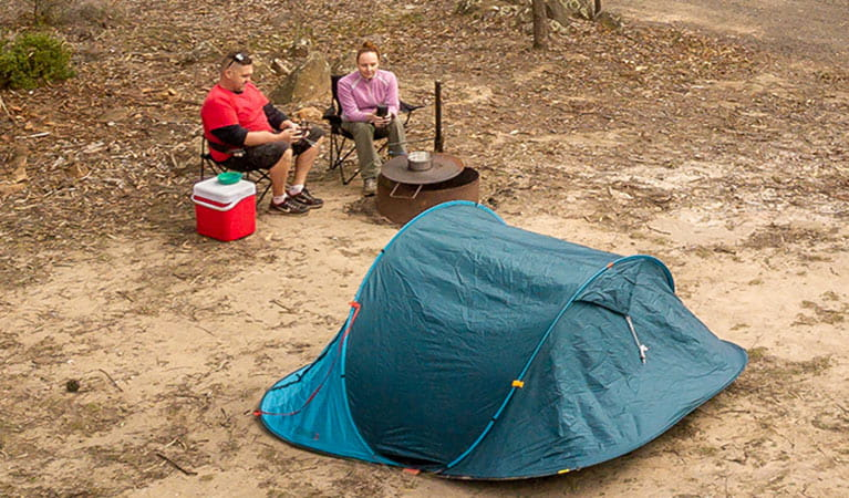 2 campers sitting next to a fire pit barbecue behind their tent. Photo: John Spencer/DPIE