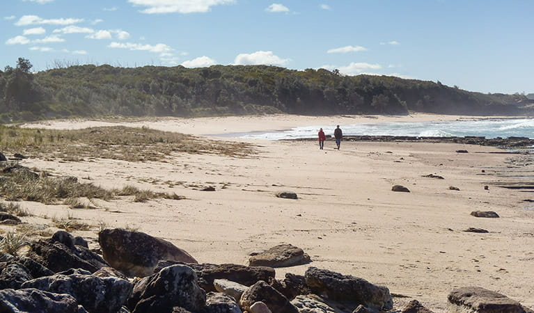 Couple walking on Monument Beach, Conjola National Park. Photo: Michael Jarman