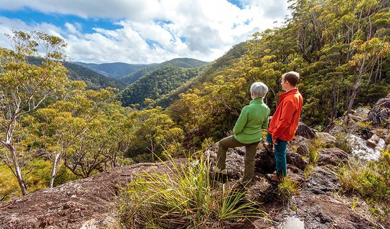 A couple looking out over the mountain range, Gibraltar Range National Park. Photo: Rob Cleary