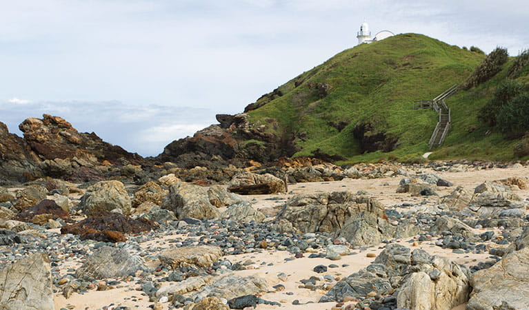 Rocky coastline with a distant lighthouse, Sea Acres  National Park. Photo: Rob Cleary