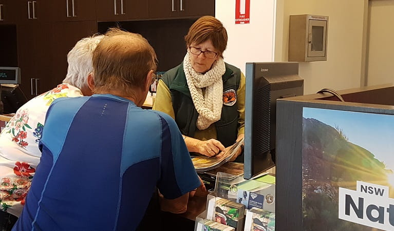 Two visitors being advised by an NPWS worker at the Warrumbungle Visitor Centre. Photo: Leah Pippos © DPIE