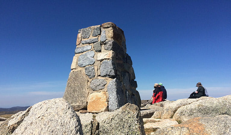 Walkers rest by the trig at the summit of Mount Kosciuszko. Photo: E Sheargold/OEH
