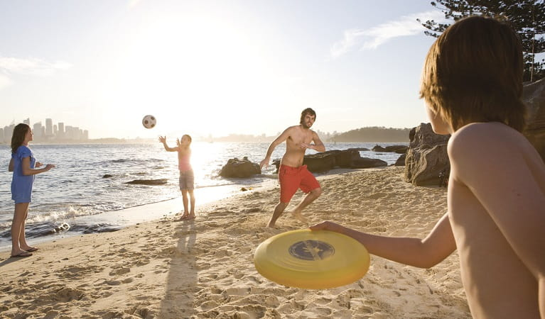 Throwing a frisbee on Shark Island, Sydney Harbour National Park. Photo: Daniel Smith/OEH