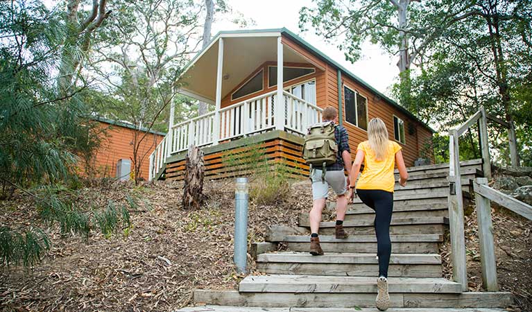People walking up cabin steps, Lane Cove Tourist Park cabins. Photo: OEH/Caravel Content
