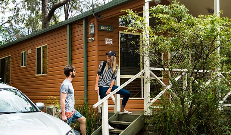 Couple arriving at Lane Cove Tourist Park cabins. Photo: OEH/Caravel Content