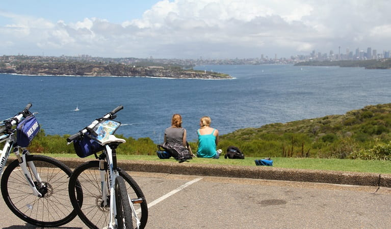 Bike riders at North Head with scenic view towards South Head and Sydney skyline, Sydney Harbour National Park. Photo: John Yurasek